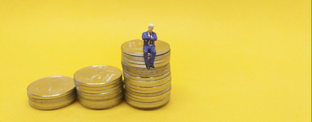 Business concept. Businessman sitting on a pile of silver coins. Stock Photo