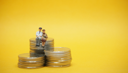 Business concept. Elderly couple sitting on a pile of silver coins.