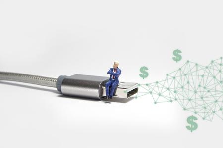 Businessman figure sitting on usb USB cable. E commerce concept. Foto de archivo - 119617513
