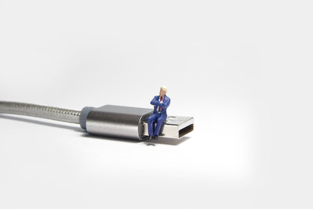 Businessman figure sitting on usb USB cable. E commerce concept.