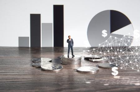 Business concept. Businessman standing on a pile of silver coins. Foto de archivo - 122372356