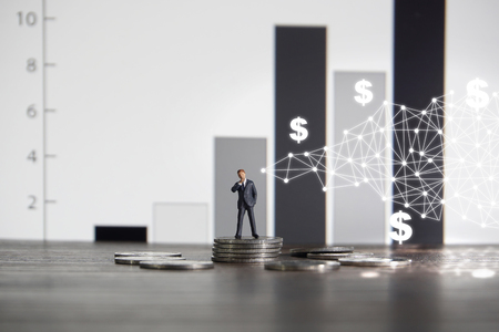 Business concept. Businessman standing on a pile of silver coins.