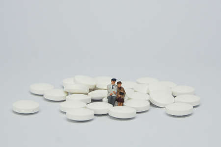 Elderly couple figure sitting on a pile of white pills.