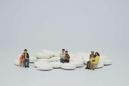 Elderly couple family figure sitting on a pile of white pills.
