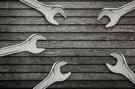 Wrenches on natural wooden background.