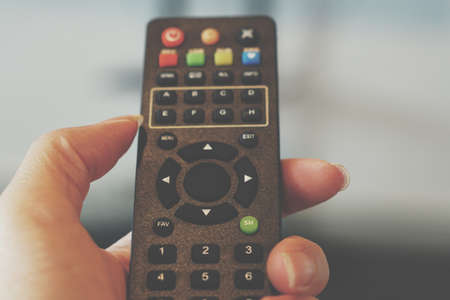 Remote control in the hand with empty middle button.