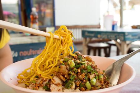 close up pork yellow noodle hot and sour soup