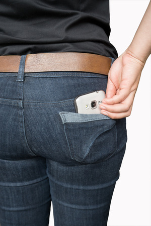 pickpocket: Woman takes out mobile phone of her pocket of jeans