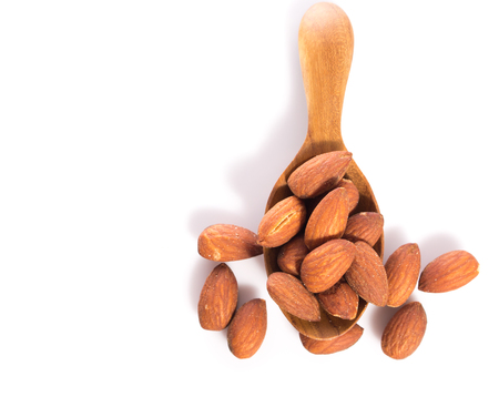 salted: salted almonds in wooden spoon on white