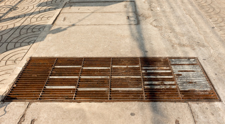 sewer: Sewer grate on the sidewalk.