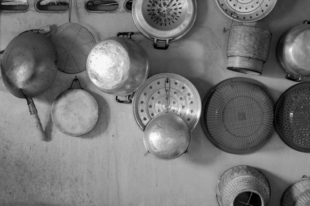 smut: kitchenware hang on cement wall,mono tone.