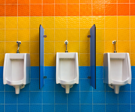 Urinals on colorful wall in public toilet photo