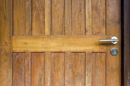 Modern style door handle on natural wooden door photo