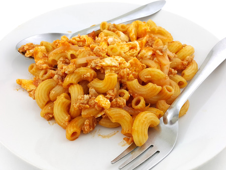 stirred: macaroni pasta in tomato sauce with chop meat Stock Photo