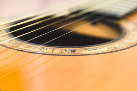 The sound hole is usually a round hole in the top of the guitar under the strings. The sound will pass through this hole. Imagens
