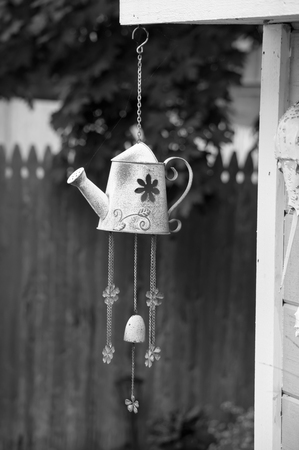 Watering can wind chime in garden Фото со стока