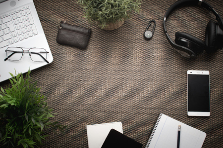 Flatlay. Top view of workspace. Travel or trip planning. Laptop mobile phone, wallet, headphones, women hat, notebook, pencil Banco de Imagens