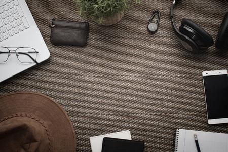 Flatlay. Top view of workspace. Travel or trip planning. Laptop mobile phone, wallet, hat, headphones, notebook, pencil