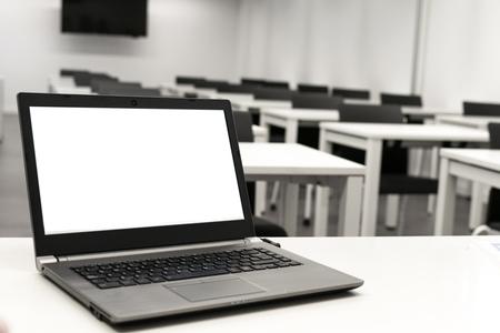 Computadora portátil, negocios en línea, trabajo del maestro en el aula. Computadora portátil colocada sobre una mesa o escritorio ubicado en una habitación vacía.