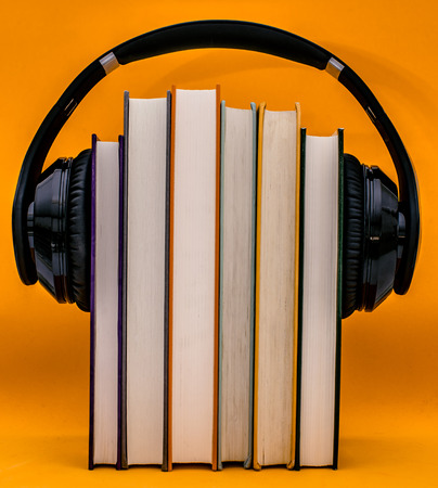 Audiobooks concept. Headphones put over book on orange background.