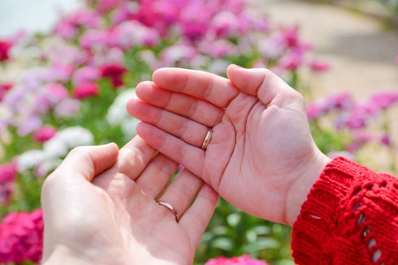 Hands of married couple with wedding rings against pink flowers background.