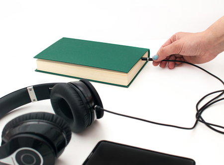 Headphones, smart phone, and book against white background with hand connecting them.