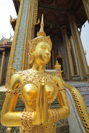 golden statue of half bird half woman figure in thai fairy tale photo