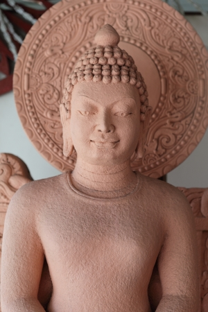 revere: pink stucco buddha sculpture with circle disk of enlightenment in background Stock Photo