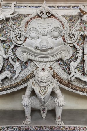 white stucco statues of thais tale monsters decorated in buildings interior  photo