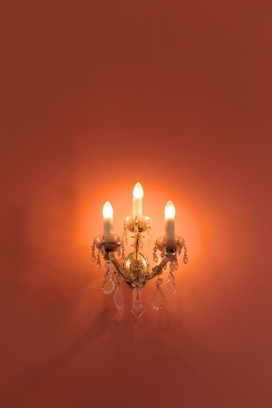 vividly: beautiful candleholder with electrical candles on vividly orange wall Stock Photo