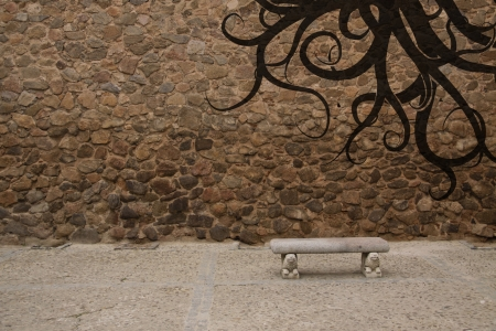 Old stone wall with bench and graffiti Stock Photo - 13990732