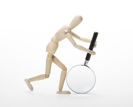 Wooden man with magnifying glass photo