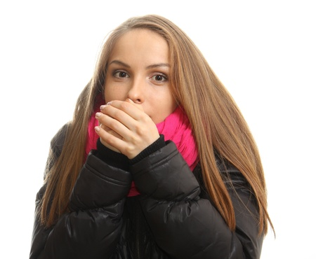 Young woman in winter tries to warm up her hands, isolated photo