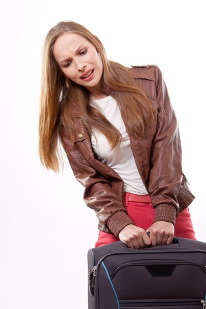 woman lifts a heavy suitcase photo