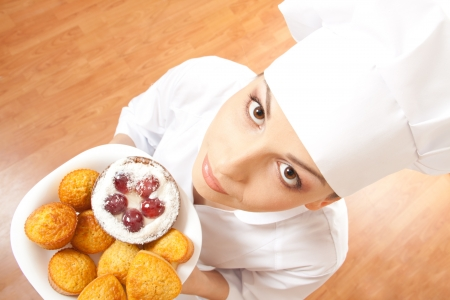Woman chef holding tray of cookies  photo