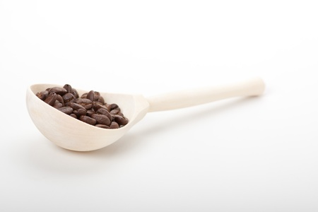 wooden spoon with coffee beans, isolated on white photo