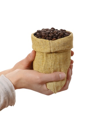 Small bag of coffee beans in female hands photo
