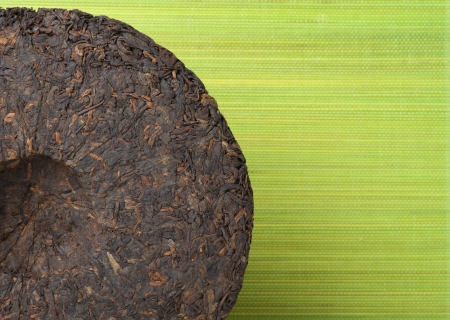 Disc of puer tea on green background photo