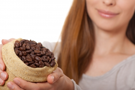 woman holding a small bag of coffee beans photo