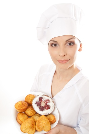 Woman chef in uniform holding tray of cookies  photo