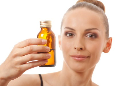 woman holding a bottle of medicine, isolated on white background photo