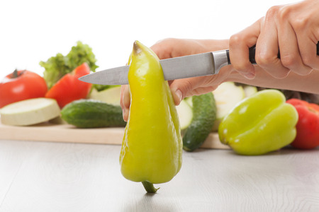 Female hands with knife, cutting fresh green pepper photo
