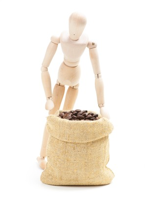 Coffee beans in burlap sack and wooden man, isolated on white photo