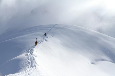 Skiërs beklimmen van een besneeuwde berg Stockfoto - 25729552