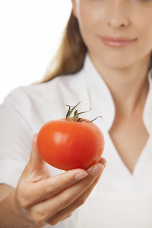 isoladed: Smiling woman cook with red tomato, isoladed on white background Stock Photo