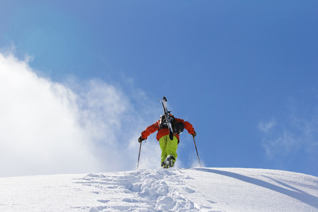 Skier climbing a snowy mountain photo