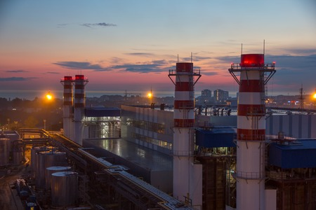 fuel and power generation: pipes of thermal power plant and and city in the evening