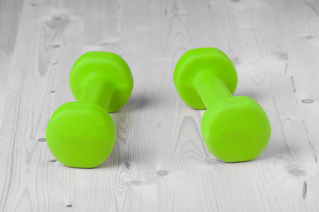 small green dumbbells on wooden surface photo