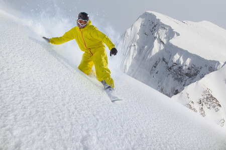 moving down: Snowboard freerider moving down in snow powder Stock Photo