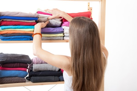 Young caucasian woman standing near the wardrobe